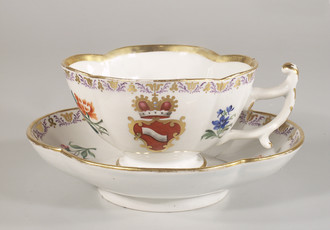 Cup and saucer with painted heraldic motif